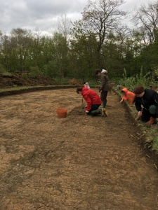 Trench six on day one with students at different stages of cleaning the context with trowels.
